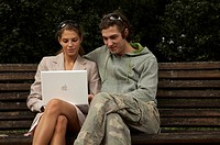 young couple with an laptop in the park