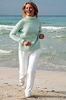 Jogging woman in turquoise sweater at the sea