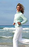 Woman in turquoise pullover at the sea