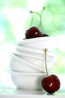 Stack of white bowls and cherries