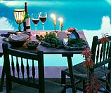 Diner table next to the swimming pool with wine, cheese, bread, grapes and candlelight