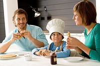 Mid adult man and a young woman having breakfast with their son (thumbnail)
