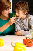 Young woman feeding basil to her son (thumbnail)