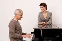 Mature man playing a piano and a mid adult woman standing near him