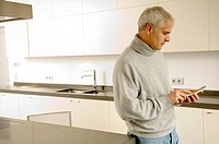 Mature man standing in the kitchen and text messaging on a mobile phone