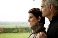 Mature man and a mid adult woman looking out through a window