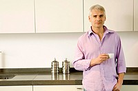 Portrait of a mature man holding a cup of tea in the kitchen (thumbnail)