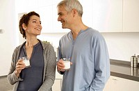 Mature man and a mid adult woman holding glasses of milk