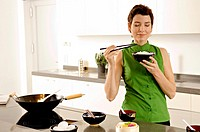 Mid adult woman smelling a bowl of rice in the kitchen