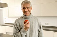 Portrait of a mature man holding an apple