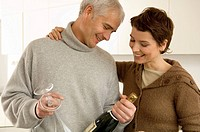 Mature man and a mid adult woman looking at a champagne bottle