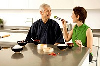 Mid adult woman feeding food to a mature man in the kitchen