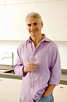 Portrait of a mature man holding a glass of water in the kitchen