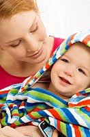 Close_up of a young woman wrapping her son in a towel and smiling