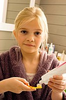 Close_up of a girl holding a toothpaste and a toothbrush