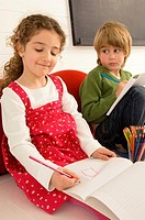 Girl drawing on a notepad and her brother looking at her