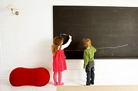 Two children drawing on a blackboard