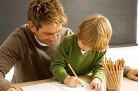 Mid adult man helping his son in drawing