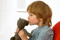 Side profile of a boy kissing a teddy bear