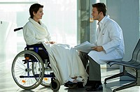 Side profile of a male doctor talking with a female patient