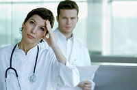 Female doctor looking worried with a male doctor standing behind her
