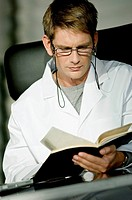 Close_up of a male doctor sitting at a desk and reading a notebook