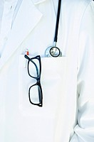 Close_up of eyeglasses and a pen in a lab coat of a doctor