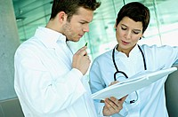Close_up of two doctors discussing a medical record