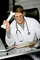 Close_up of a male doctor sitting at a desk and holding a bone