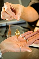 Close_up of a woman's hand holding a dowsing pendulum over a woman's palm