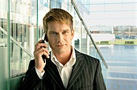 Portrait of a businessman talking on a mobile phone at an airport