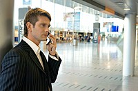 Side profile of a businessman talking on a mobile phone at an airport