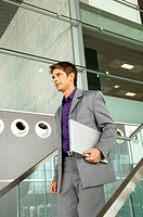 Businessman holding a laptop and walking down a staircase