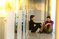 Two businessmen sitting in a corridor and talking with each other