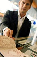 Businessman showing his passport at the airport check-in counter (thumbnail)