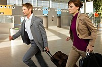 Businessman and a businesswoman rushing with their luggage at an airport