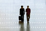 Mid adult man walking with a young man at an airport (thumbnail)