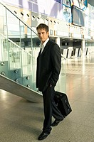 Portrait of a businessman carrying a luggage at an airport