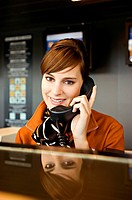 Portrait of an airline check_in attendant talking on the telephone