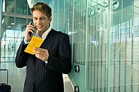 Businessman holding an airplane ticket and talking on a mobile phone at an airport