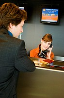 Businessman standing at an airport check_in counter while the check_in attendant talking on the telephone