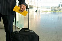 Mid section view of a businessman holding a luggage and an airplane ticket