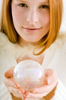 Portrait of a young woman holding a crystal ball