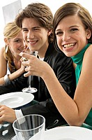 Two young women with a teenage boy at a dinner party