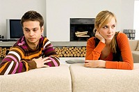 Young couple leaning on a couch and looking serious