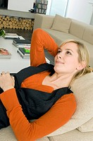 Close_up of a young woman lying on a couch and thinking