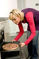 Young woman putting a tray of pizza into an oven