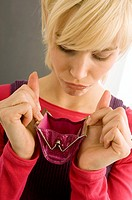 Close-up of a young woman looking into an empty purse (thumbnail)