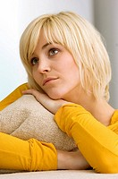 Close_up of a young woman hugging a cushion and thinking