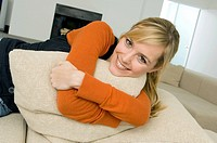 Portrait of a young woman hugging a cushion and smiling